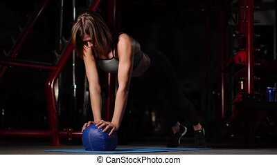 A brunette athletic builds push-ups on a mache in the gym...