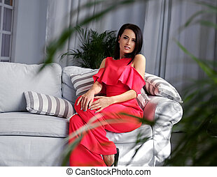 A brunette female dressed in a red evening dress sits on a coach.