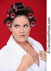 A brunette in the morning with hair rollers on.