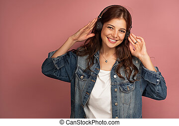 A brunette on a pink background in a denim shirt is smiling and looking into the camera while holding the headphones in her hands