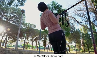 A brunette Portuguese woman, middle aged, doing a straps pull-up, in a park on a sunny morning. High quality 4k footage