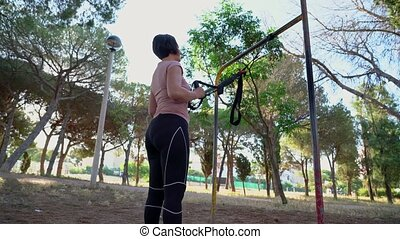 A brunette Portuguese woman, middle aged, doing a straps squat, in a park on a sunny morning. High quality 4k footage