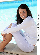 A brunette sitting by the swimming pool.