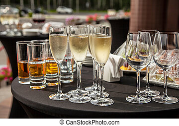 A buffet table on the terrace with glasses of champagne. Glasses of champagne stand on the terrace table.