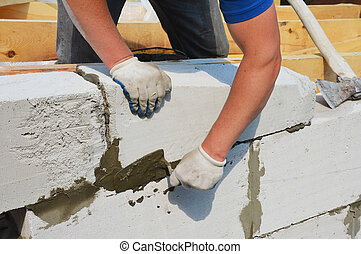 A building contractor is constructing a wall from autoclaved aerated concrete blocks using a trowel and an axe, attaching concrete blocks of home addition to wooden roof beams.