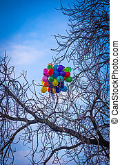 A bunch of bright colored balloons stuck on a tree in Prague
