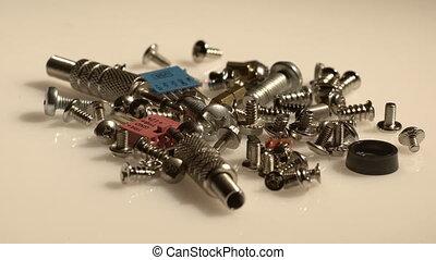 A bunch of computer screws in grey tones