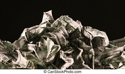 A bunch of crumpled fifty-dollar bills rotate on a black...