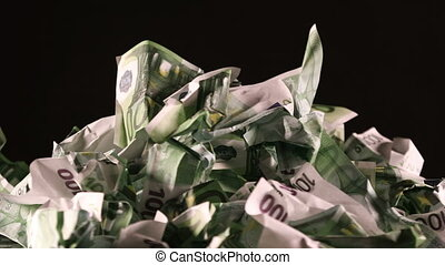 A bunch of crumpled one hundred Euro banknotes rotate on a...