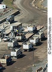 Dump trucks lined up at a rock quarry