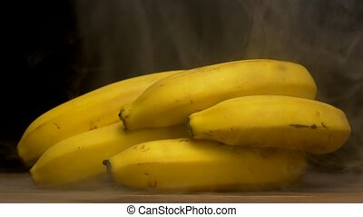 A bunch of fresh bananas on a black background from which...