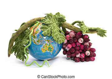 A bunch of grapes from felted wool next to a globe on a white background