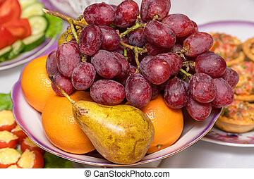 A bunch of grapes, pear and orange on the plate