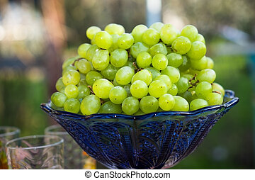 A bunch of green grapes in a blue vase