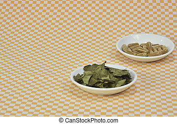A bunch of green tea, on leaf capsules or pills on dishes.