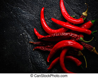 A bunch of hot chili peppers. Dark stone background from slate.