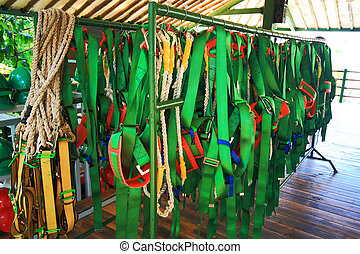 a bunch of human harnesses hanging on a rack