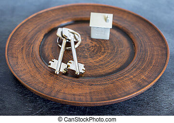A bunch of keys lie on a vintage plate, along with an imitation of the house in the form of a metal layout.