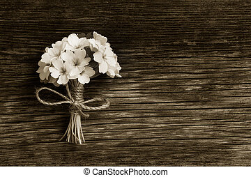 a bunch of primroses tied with string on an old wooden board in the cracks