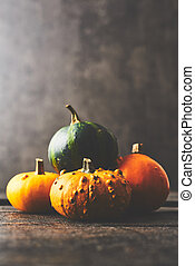 A bunch of pumpkins on black wooden rustic table over dark concrete background