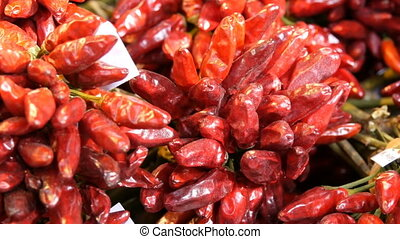 A bunch of red hot chili peppers on the market counter. - A...