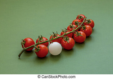 A bunch of ripe red cherry tomatoes with a white ball on a green background