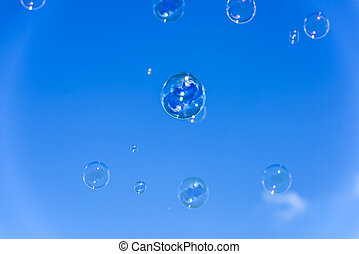 A bunch of soap bubbles flying up into the blue sky