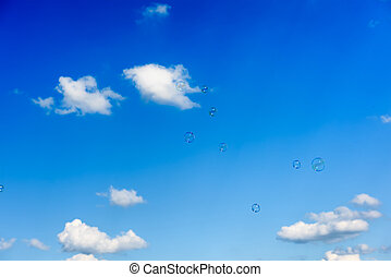 A bunch of soap bubbles flying up into the dark blue sky
