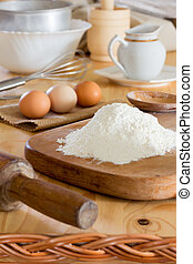 a bunch of white wheat flour, raw eggs, rolling pin, stainless steel whisk and other utensils on the kitchen table. close-up, selective focus. rustic style