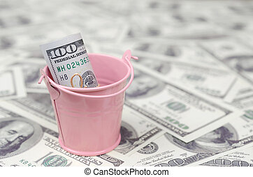 A bundle of US dollars in a metal pink bucket on a set of dollar bills