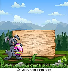 A bunny holding Easter Egg with blank wooden sign