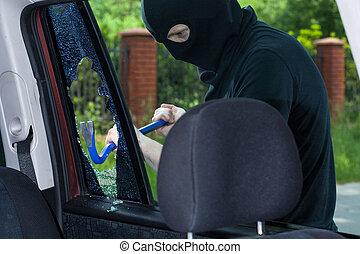 A burglar breaks a window with a crowbar