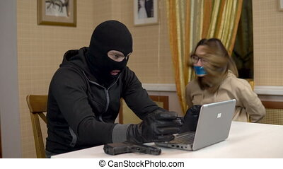 A burglar is trying to break into a laptop by taking a young...