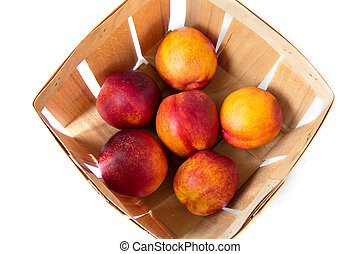A bushel basket full of fresh picked yellow peaches, view from above
