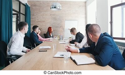 A business conference. A man drawing a charts on the board....