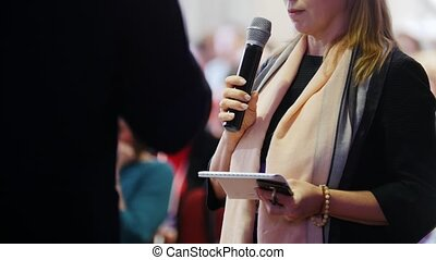 A business conference. A woman reading something holding a mic