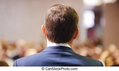 A business conference in the hall. A man talking on the...