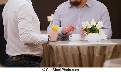 A business conference. People standing to the table. A man holding the glass of juice