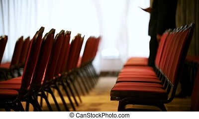 A business hall. An empty red chairs in the hall. Mid shot
