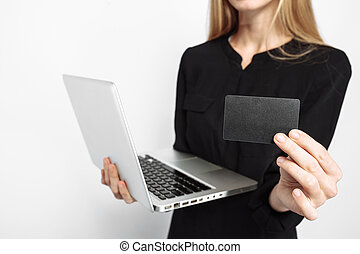 A business lady in a black dress, with a laptop, and holding a credit card, is getting ready for Black Friday. Black Friday, business, shopping