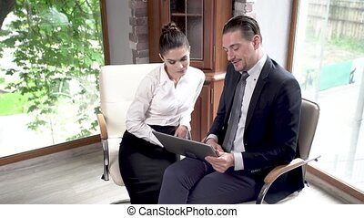 A Business Man And a Business Woman are Sitting in a Conference Room and are Looking at a New Project on a Map-Case.