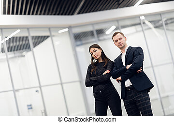 A business man and woman standing back to back with smiles on their faces