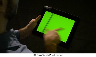 A business man holds green screen tablet pc in hand and fast swiping on the display