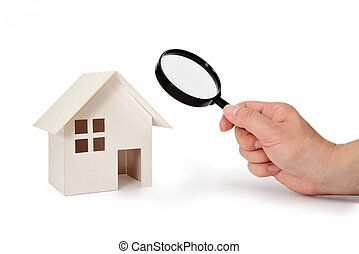 A business man looking at a model house holding a magnifying glass in his hand.