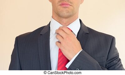 A business man nervously adjusts his red tie. 4k, slow...