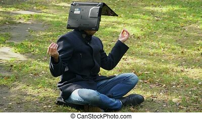 A business man sits in a coat in a Lotus position with a laptop on his head