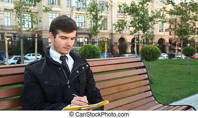 A business man sits on a bench and writes something
