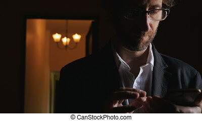 A business man working late at night uses app on his phone -...