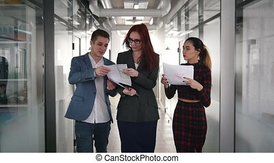 A business people walking through the corridor. People showing the documents to their woman chief