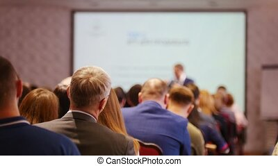 A business presentation in the hall. People sitting on the chairs and looking at the screen